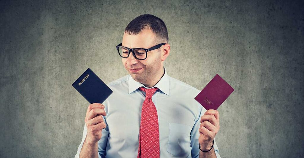 man with glasses wearing red tie holding two passports, benefits to alternative citizenship