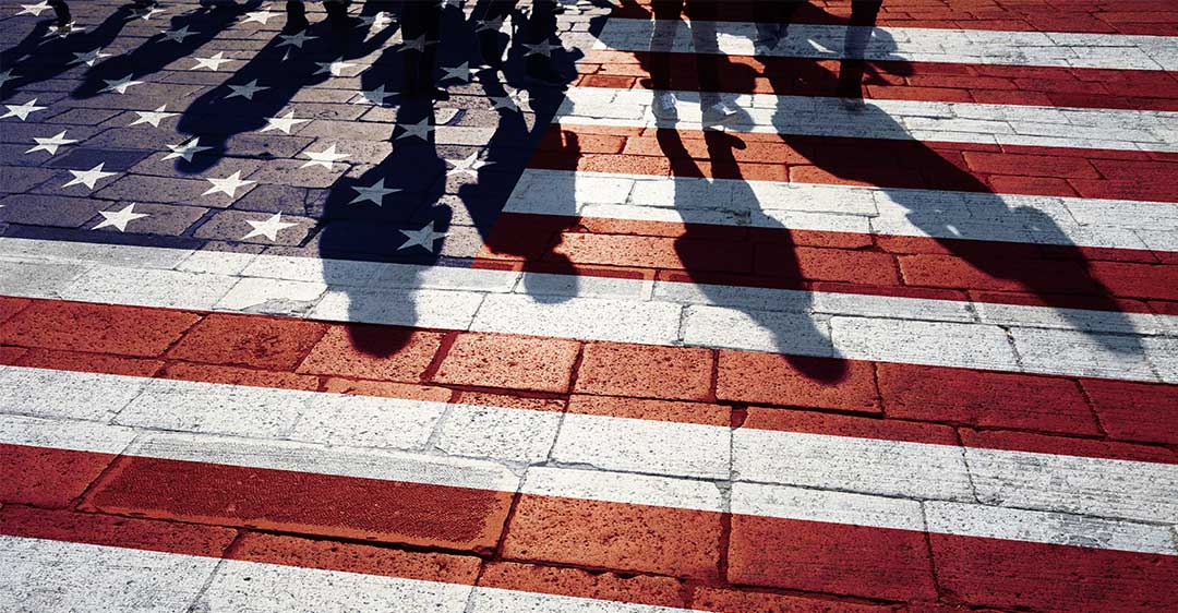 us flag painted on brick walkway with shadows of people walking, biden immigration rules impact business, international business