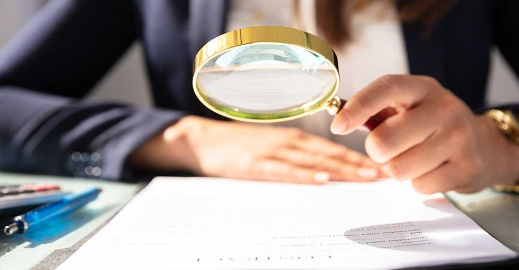 business woman with magnifying glass, looking at a document, why contract typos and grammatical errors can spell disaster