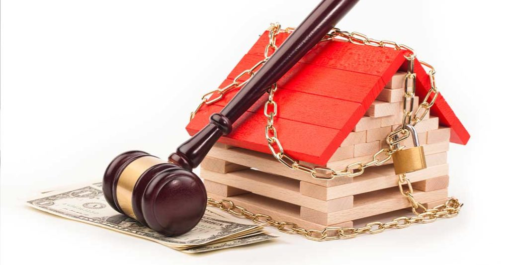 miniature block house with chains and padlock, gavel and cash, how to stop an illegal lien
