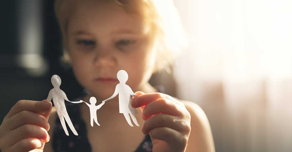 child holding paper cut out of family, international child custody, international family law, international parental child abduction, international parental child kidnapping