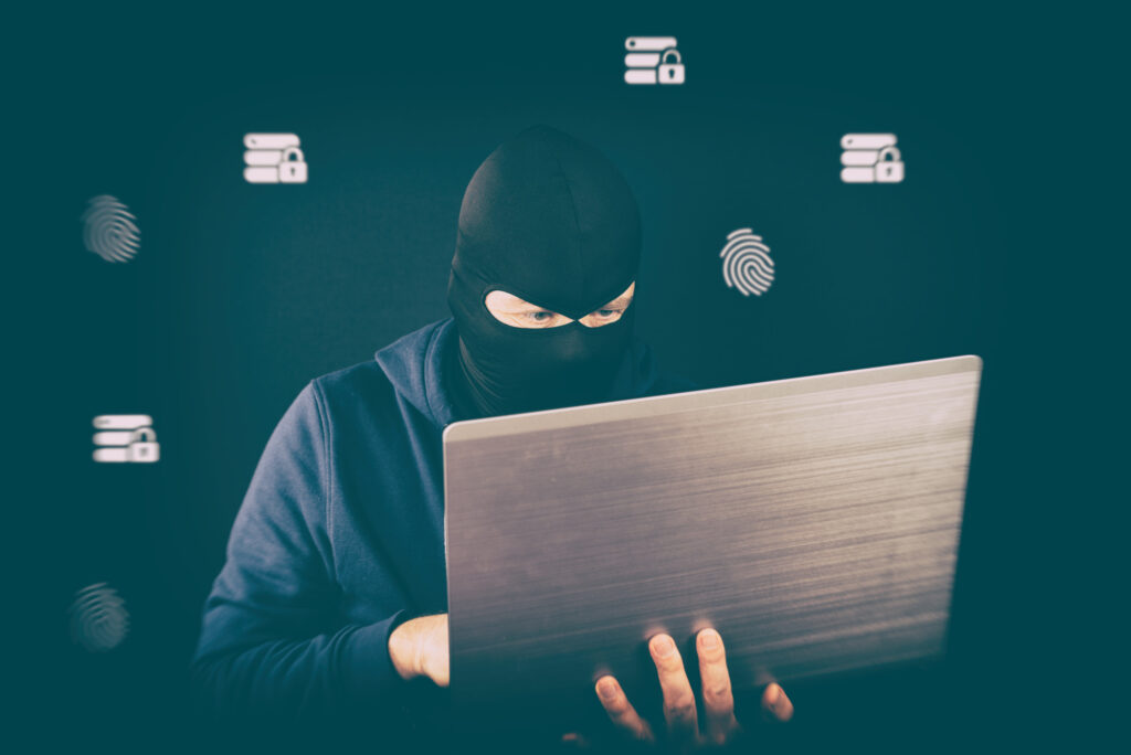 masked man on laptop, email fraud, protect your business form email fraud as employees work from home