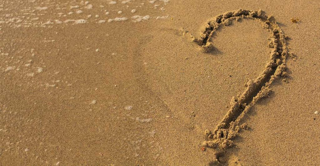 beach sand, water washing away half heart drawn in sand, separation tips and tricks for expats
