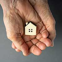 elderly woman hands holding a little toy house, property inheritance, summary administration, small estate